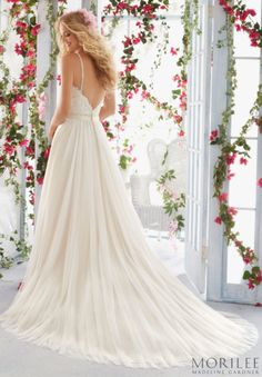 Morilee by Madeline Gardner Beach or Destination Wedding Dress, style 6818. A Scalloped Alencon Lace Edged A-Line flowy Tulle gown. An Open V Back with thin crystal beaded straps and a sweetheart neckline.