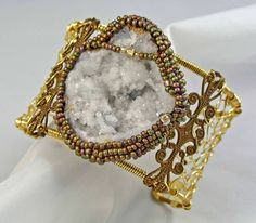 Wire wrapped cuff with a geode enclosed by off-loom bead weaving. Beadwork by cgm