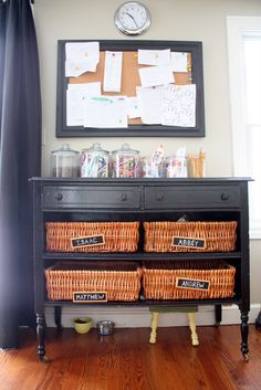 a dresser with baskets in the kitchen, labeled with each kid's name, for all the kid's stuff you find lying around that has to go up to their rooms.