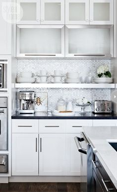 Such a cute kitchen and a great way to run stock cabinets to the ceiling and a shelf under rather than hanging them with that cheap, awkward empty space above!: