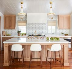 """""""The kitchen started out as a basic white kitchen.We wanted it to feel more in line with the harder lines of the house and we designed it out of quarter sawn oak, which is very durable, and quartz countertops.Also, natural wood cabinets are morelikely to avoid the stains that come from having small kids running around,"""" Howard says. Light fixtures, The Urban Electric Co.; Barstools, Design Within Reach;Hood,Silestone;Range,Wolf; Fauc..."""