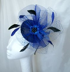 Royal Blue & Navy Elizabeth Blusher Veil Crinoline & Feather Fascinator Mini Hat. Order Now from www.indigodaisyweddings.co.uk Specialising in stunning bespoke cocktail fascinators and formal hats in a wide range of colours, perfect for Royal Ascot and The Kentucky Derby. Plus all your wedding floral accessories including shoe clips, vintage flapper bands, feather and flower fascinators, feather fans, fairy wands, wrist corsages, wedding bouquets & buttonholes. Worldwide Delivery.