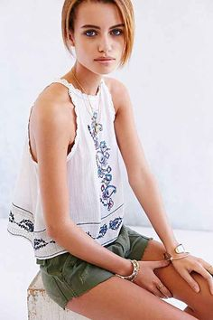 Lightweight cotton gauze tank top from UO's boho-chic Ecote label with metallic-accented embroidered detailing along the front and hem. Topped with crochet trim along the high neckline and dropped armholes. Finished with a keyhole cutout and button closure at the back. Semi-sheer.