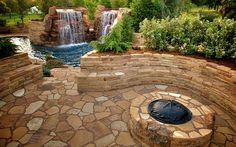 Flagstone patio and stone bench, retaining walls with fire pit.  Stone steps lead down to pool area
