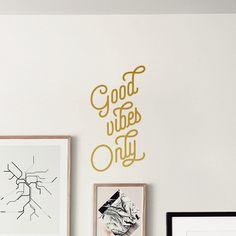 """Adesivo de parede com frase da Pequenas Causas: """"Good vibes only"""" (algo como """"só energia boa"""")."""