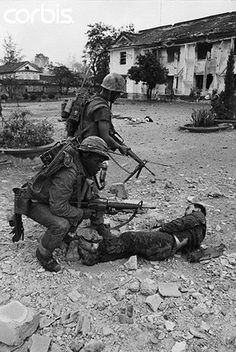 12 Feb 1968, Hue, South Vietnam --- US marines with M-16s search and secure a wounded enemy soldier during fighting at Hue, South Vietnam. --- Image by © Bettmann/CORBIS