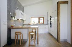 (STENA) Kuchyňská linka je provedena z MDF desek s vysokým leskem a zakončena dubovým barovým stolem. Šedé obložení boční stěny vypadá jako pohledový beton, jde však o laminované desky.
