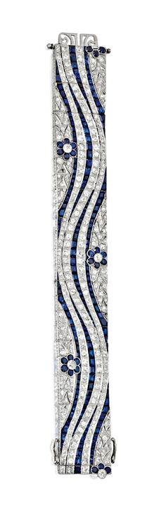 PLATINUM, SAPPHIRE AND DIAMOND BRACELET, CIRCA 1935. The wide articulated band of wave design accented by flowers, set with old European-cut and single-cut diamonds weighing approximately 15.00 carats, and calibré-cut sapphires, length 7½ inches.