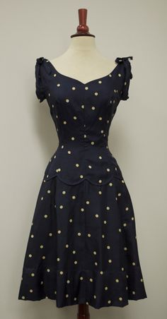 Navy silk polka-dot dress, c. 1940's. From the sweetheart of a neckline, the bodice is made even cuter with the gathers and bows at the shoulders. Fashioned with princess seams that cinch in, the (drop) waist is further embellished with a decorative seam that scallops around the dress, so cute.