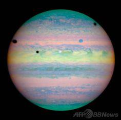 米航空宇宙局(NASA)が公表した、ハッブル宇宙望遠鏡(Hubble Space Telescope)撮影の木星の衛星。イオ(Io)とガニメデ(Ganymede)、カリスト(Callisto)の3衛星が並ぶ珍しい現象を示している。写真中央の白い円がイオ、右上の青い円がガニメデ。カリストは画面の右の外側にありこの写真には写っていない。木星の表面に見える黒い円は右からそれぞれカリスト、イオ、ガニメデの影(2004年11月9日入手)。(c)AFP/NASA ▼6Jul2014AFP|【特集】木星 ─ ガスが渦巻く太陽系最大の惑星 http://www.afpbb.com/articles/-/3017992?ctm_campaign=must_read #Jupiter