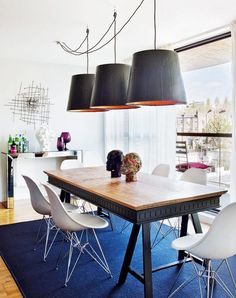 Wooden dining table with large pendants and a blue rug.