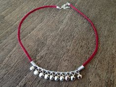 Jingle Bell Wire Wrapped Woven Bracelet: Jingle bell, aluminium, wire wrapped necklace, with hand woven wine red cord and adjustable lobster clasp fastening.