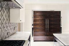 Macassar ebony veneered wave doors on Subzero refrigerator and freezer with chrome surround and white lacquer cabinetry.