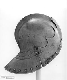 Sallet with comb, southern Italian, c.1490.Rounded skull with comb, a reinforcing plate with deeply cusped upper edge riveted to the brow. Laminated neck-guard of three plates the outer or tail plate being of large size.  All three lames are restorations.