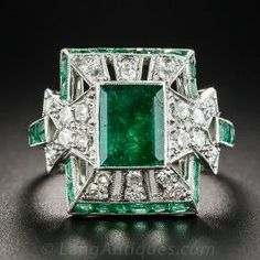 A rich deeply saturated green emerald, weighing 1.35 carats, crowns this exemplary and exotic Art Deco showstopper hand-fabricated in platinum. The multidimensional geometrically fashioned pagoda style design glitters all around with small brightly twinkling round diamonds, outlined with bright green calibre emeralds, for a striking and sophisticated effect. 5/8 inch, currently ring size 5 3/4.