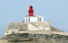 La Madonetta #Lighthouse - Bonifacio, Corsica, #France | Built in 1854, the lighthouse is perched on a white limestone peninsula on the west side of the narrow entrance to the harbor of Bonifacio. The square masonry tower, painted red, rises from the center of a one story masonry keeper's house which is painted white. The limestone cliffs have been carved into an unusual series of stripes, caves and other formations by the work of the sea. http://dennisharper.lnf.com/