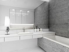 Project of a bright, modern bathroom with large mirror which scales up the space, and with capacious cupboards above built-in geberit flush tank.