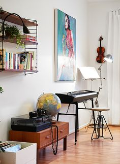 Somewhere in the living room. Violin NOT on the wall. Get a small stand for it maybe. And a radio instead of a record player.