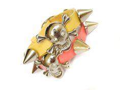 Pulseira em couro com 21cm de ponta a ponta. Spikes niquelados (não enferrujam), pingente de caveira com olhos de strass e fivela em aço com regulagem.  Preço unitário, portanto, especifique a(s) cor(es) desejada(s) no ato da compra. Cores disponíveis: Amarelo (1) Coral (1)  - Produto exclusivo Blaze - R$29,90