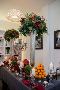 Traditional, scented Christmas with tall vases of seasonal berries, mini urns of red roses, bowls of clementines and crab apples, mini rosemary trees, clove studded oranges and bundles of cinnamon.