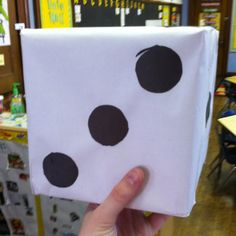 Large dice were created using cardboard, paper, and black/ white paper. You could put something inside of the box before sealing to add weight or sound to each roll.