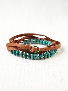 Leather wrap bracelet with turquoise and brass bead detailing and buckle closure.