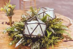 Wintry centerpieces featuring snow-white blooms in faceted terrariums | Photo by…