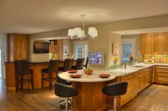 Large Kitchen - Natural cherry cabinetry, silestone countertops, bar area with seating, seating around peninsula, stainless steel appliances, tile backsplash