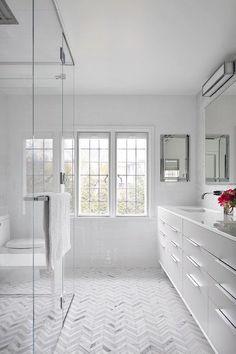 Sleek modern vanity, chevron marble floors, shower