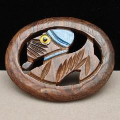 """Carved wooden oval dog pin with blue painted accents and a glass eye. Vintage pin with C-clasp. Condition is good to very good. There are no marks or hallmarks. This wooden dog pin measures 2 1/4"""" x 1"""