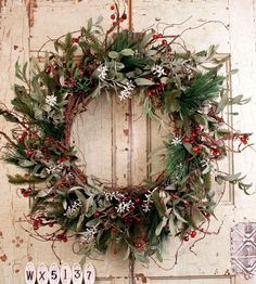 Pine, spruce, senecio and red berry wreath on a natural twig base.