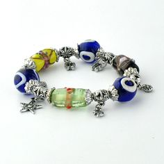 This bracelet features four glass beads of various colors, several silver charms and three glass beads that bear the Evil Eye symbol.