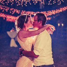 bride and groom kiss backlit