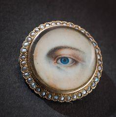 Brosch med hårslinga på baksidan Brosch av guld, ben, pärlor och hår från 1800-talets första hälft. Under den tunna benplattan med det målade ögat ligger en hårlock. Foto: Mats Landin, © Nordiska museet