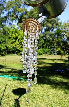 A Watering Can That Pours Crystals hanging out in the back yard off of a beautiful tree.