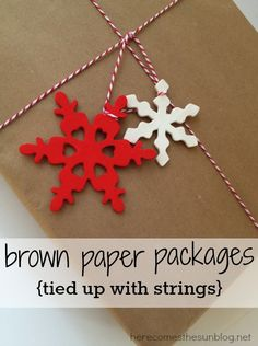 Brown kraft paper paired with red and white bakers twinr and wooden snowflakes makes beautiful DIY wrapping paper!