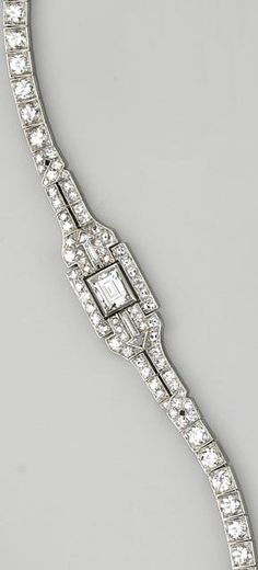 An art deco diamond and platinum bracelet centering a rectangular step-cut diamond, flanked by triangular and baguette-cut diamonds in the form of arrows, set throughout with transitional and single-cut diamonds; central diamond weighing an estimated: 0.95 carat; estimated total diamond weight: 5.15 carats; length: 7 1/4in.