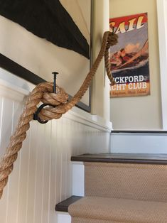 source: Kate Jackson Design    Fun nautical themed stairwell with white beadboard walls and braided jute rope banister. The stairs feature stained wood treads with a jute rug runner. The walls are adorned with a framed nautical flag and vintage sailing print.