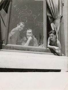 GERDA TARO:  Three men in the window of the Hotel Colón, headquarters of the PSUC, Barcelona, Spain. August 1936.  Gelatin silver print.