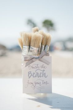 Paintbrushes with a sign indicating guests should take one to clean the sand off their toes. Perfect for beach weddings
