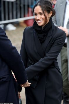 Harry and Meghan were given a rapturous welcome as they began a day trip to Cardiff - and she looked delighted by the warm reception