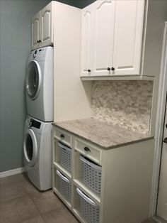 Solution to a small laundry room. Stacked washer and dryer, storage cabinets, and laundry basket storage/sorting area finished off with a beautiful slab of granite, simple hardware, and stone backsplash.