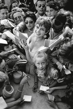 Brigitte Bardot and Brigitte Fossey signing autographs at Cannes (1955).