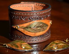 On sale! Reduced from $100 to $75! This wood tone Ojitas Acorn Brown Leather Cuff features a hand braided elevated appliqué that reveals a hidden splash of metallic green color, echoing the tiny green leaves (ojitas) that decorate the band. The effect is unique and reveals the richness and versatility that can be found in leather. The cuff is lined with leather and the edges are burnished. The entire perimeter of the cuff is beautifully hand laced with a light, natural tone leather lace that…