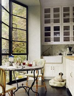 rattan bistro chairs + glass door to the ceiling upper cabinets + industrial iron windows