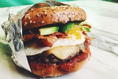 This ultimate breakfast burger is topped with avocado, egg, gouda, tomato jam and bacon. #Recipes #HowTo