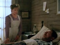 Christy approaches her father's bedside.