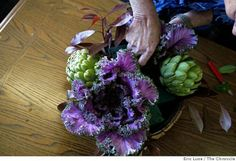 Ron Morgan, tabletop designer works on his arrangement that includes asparagus, apple, pepper and artichoke photographed in San Francisco ...