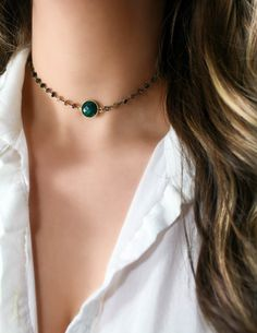 A gorgeous micro faceted emerald lyes center among a glittering strand of tourmaline stones wrapped in oxidized sterling silver. Finished with a 14k