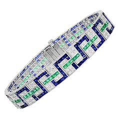Vintage Style Geometric Emerald and Sapphire Bracelet. Platinum vintage style geometric bracelet consisting of 156 full cut diamonds having a total weight of 2.05 carats, set with 65 square cut emeralds and 169 square cut sapphires having a total weight of 18.80 carats